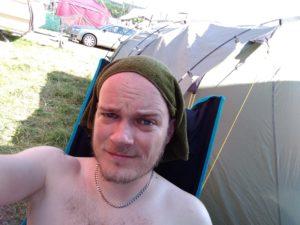 Jan sitzt mit nassem Tuch auf dem Kopf iim Schatten