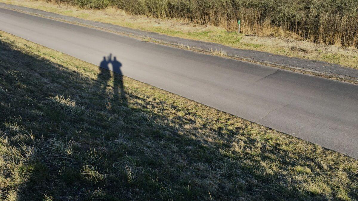 Man sieht die Schatten von Janna und Jan wie sie winken auf einer Straße